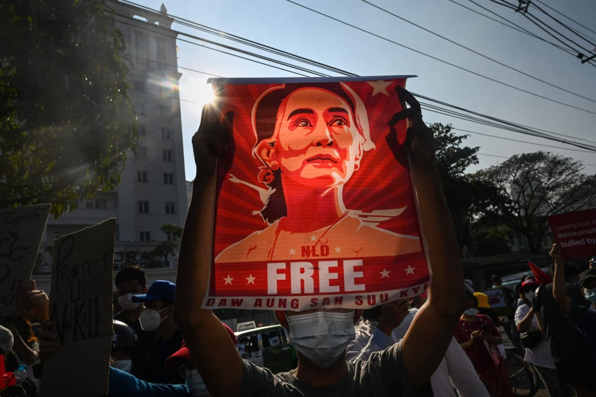 Mielenosoittaja nostaa julistetta Aung San Suu Kyistä.