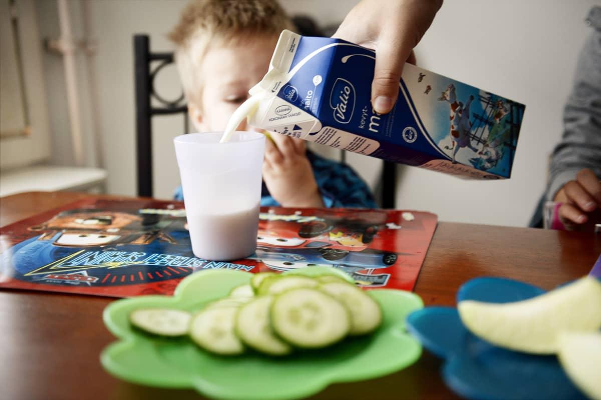 Pikkupoika syö välipalaa kotona.