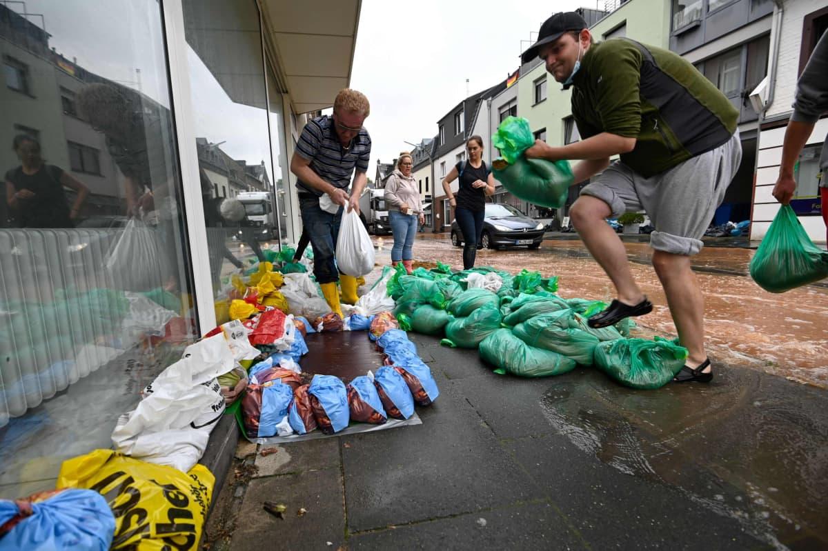 Ihmiset kasaavat hiekkasäkkejä estääkseen tulvaveden pääsyä talon sisätiloihin.