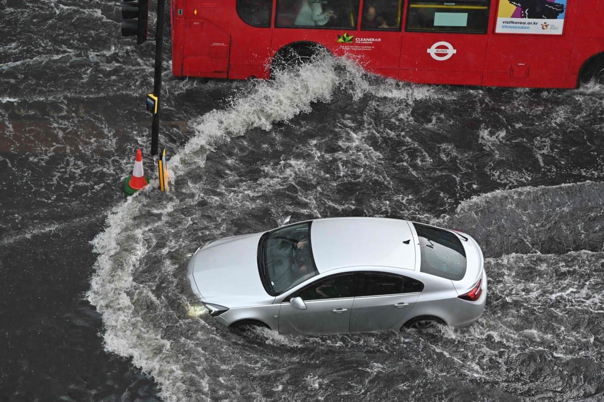 Auto ajaa tulvivalla kadulla.