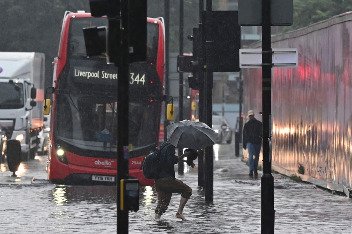Mies kahlaa tulvivalla kadulla.