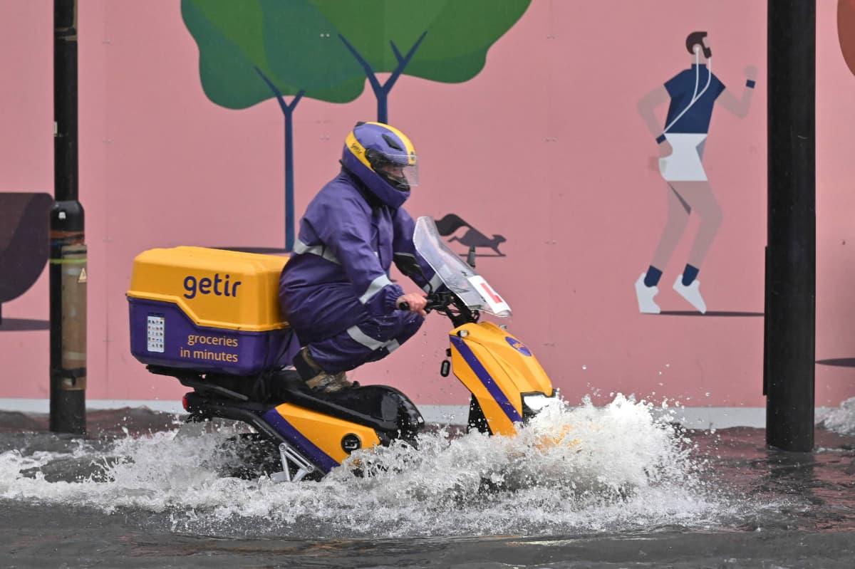 Skootteri ajaa tulvivalla kadulla.
