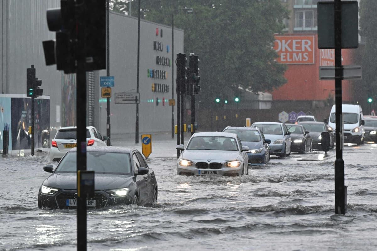 Autoja ajaa tulvivalla kadulla.