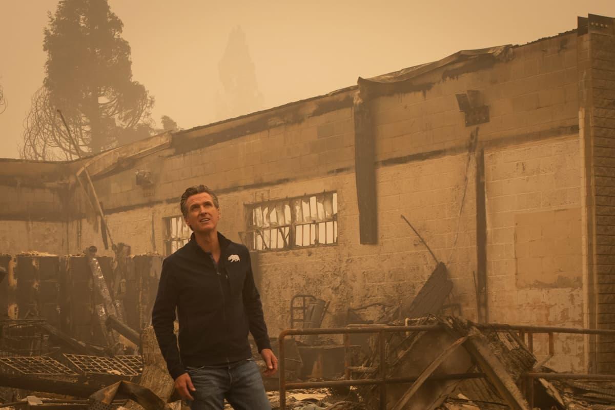 Kalifornian kuvernööri Gavin Newsom seisoo palaneen rakennuksen edessä Kalifornian Greenvillessä.