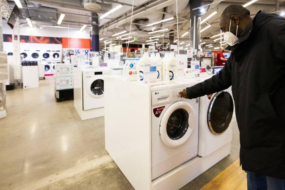 Henkilö tutkii myynnissä olevaa pesukonetta.