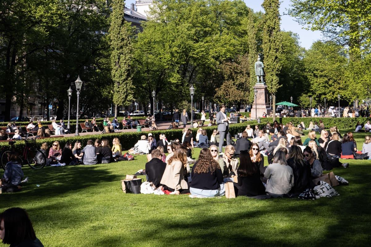 Ihmisiä nauttimassa aurinkoisesta päivästä puistossa.