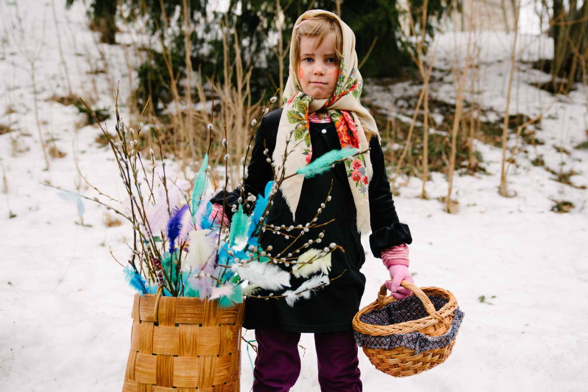 Tyttö pääsiäiskorin kanssa kadulla