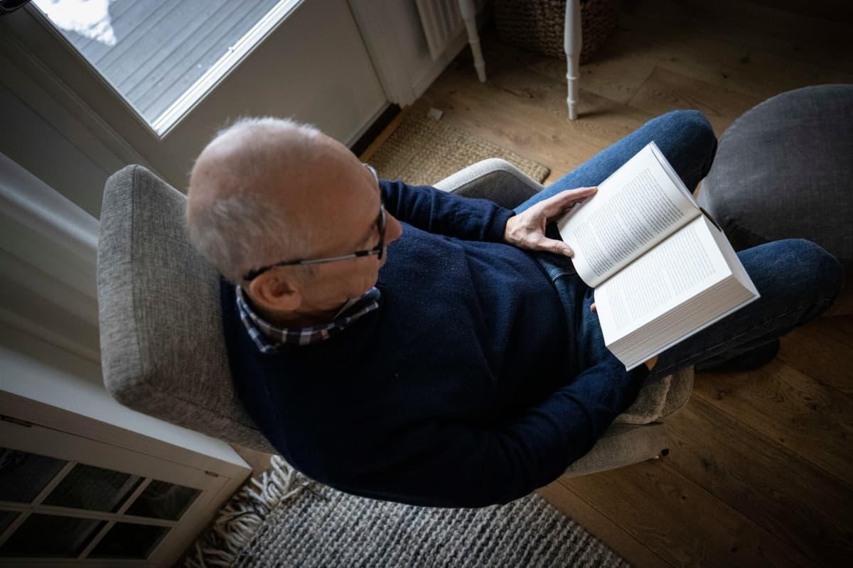 Vanhempi mies lukee kirjaa. Kuvituskuva