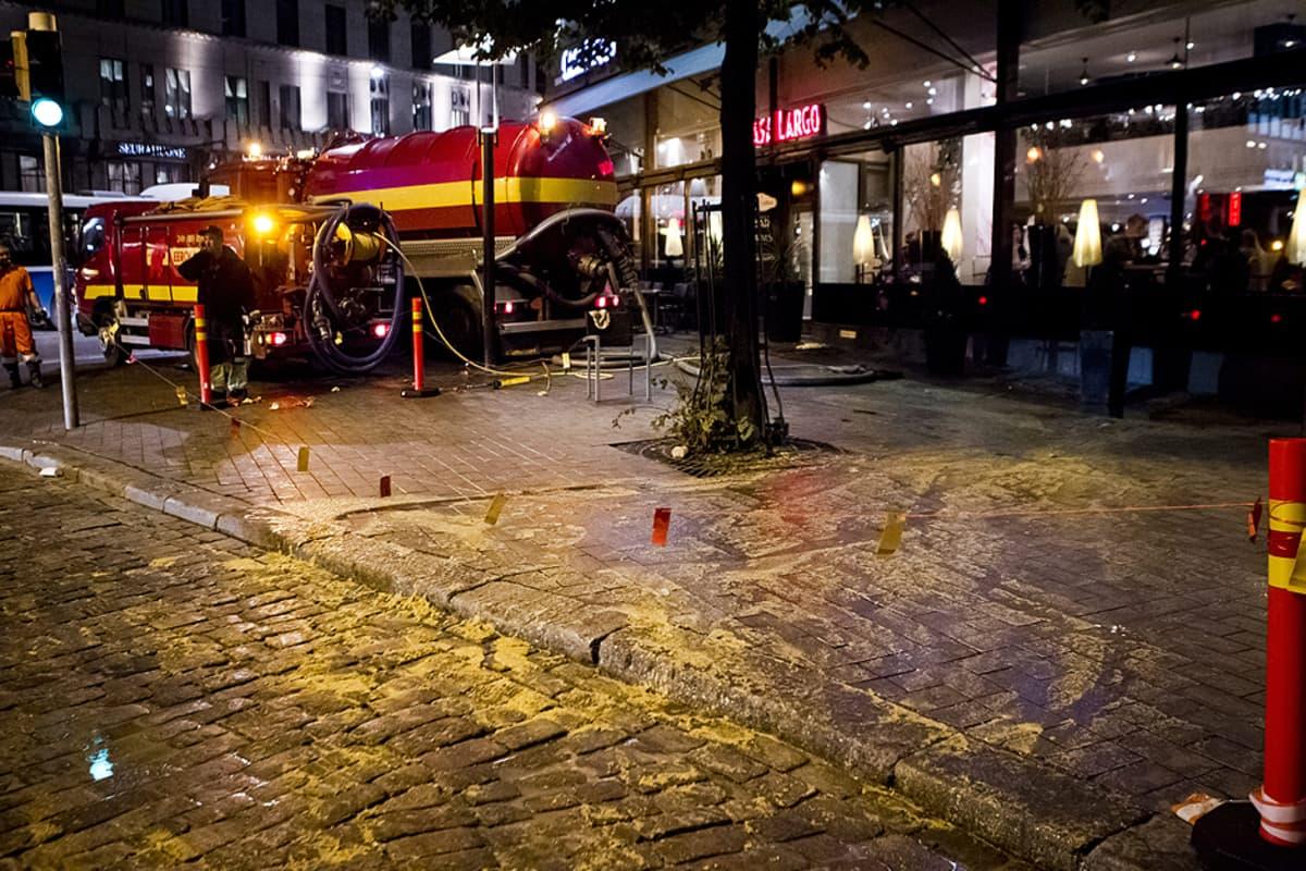 Pumppuauto siivoaa kadulle tulvinutta viemärilietettä Helsingin keskustassa.