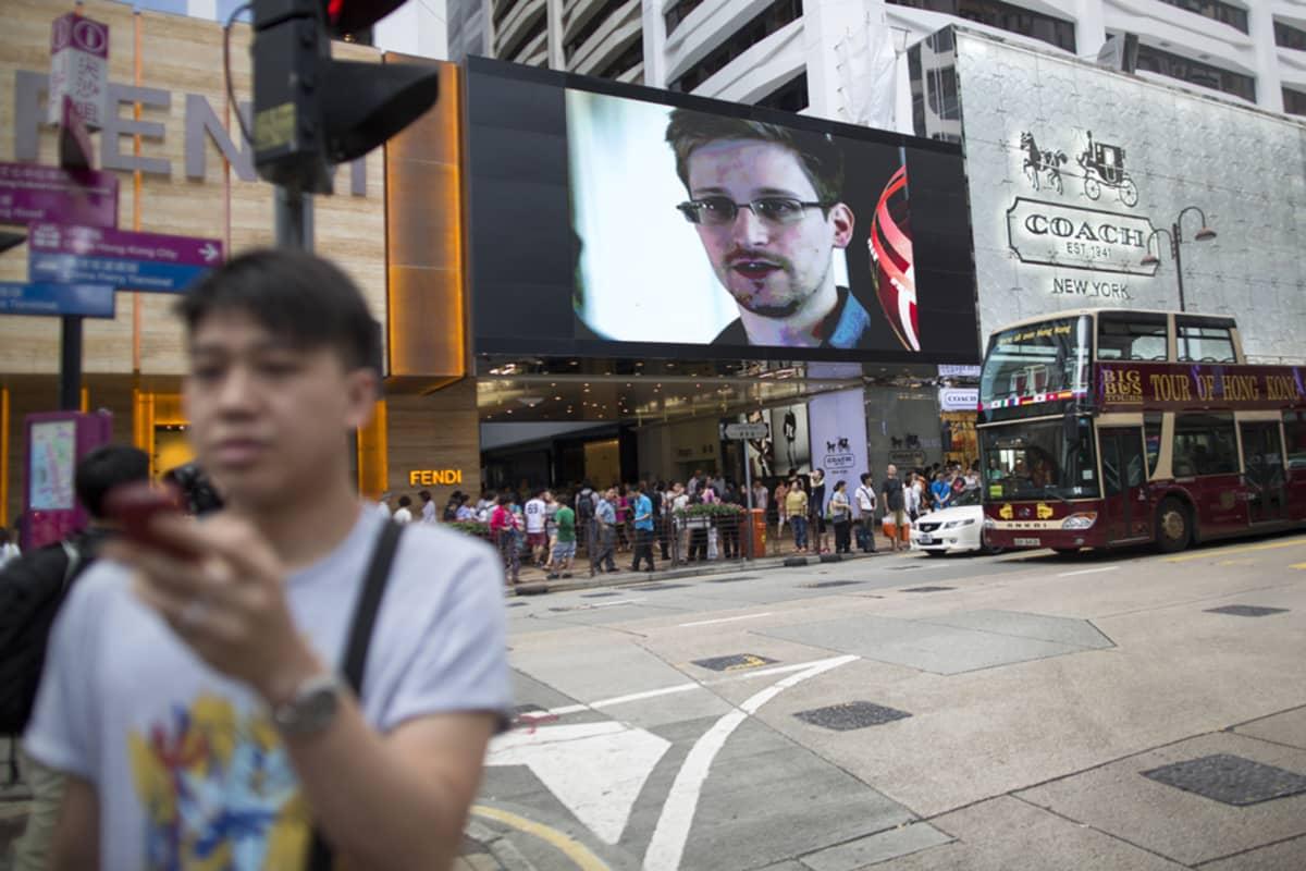 Hongkonglaisessa uutiskatsauksessa pyöritetään Edward Snowdenin arkistokuvaa samaan aikaan, kun paikallinen kadulla kävelijä seuraa oman kännykkänsä näyttöä.