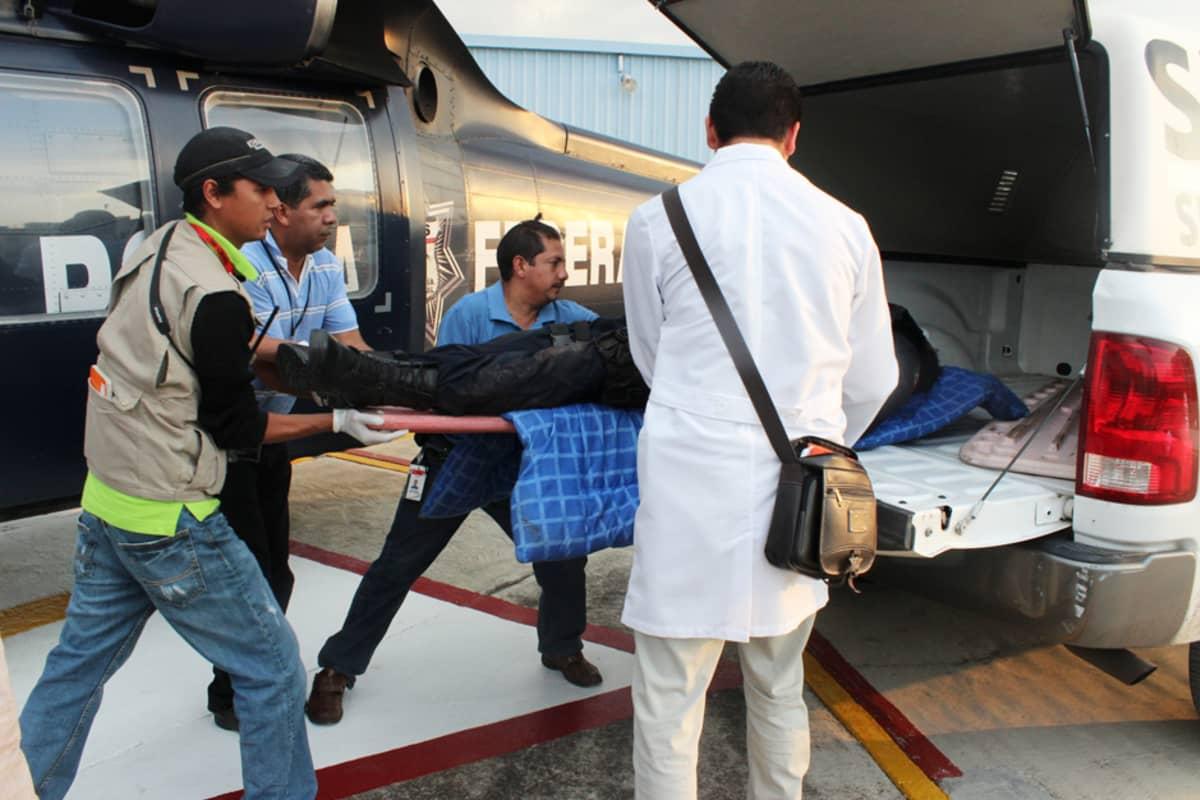 Huumejengien ja poliisin yhteydenotossa menehtyneen viranomaisen ruumis kuljetettiin pois rikospaikalta lähellä Arteagin kaupunkia 23. heinäkuuta.