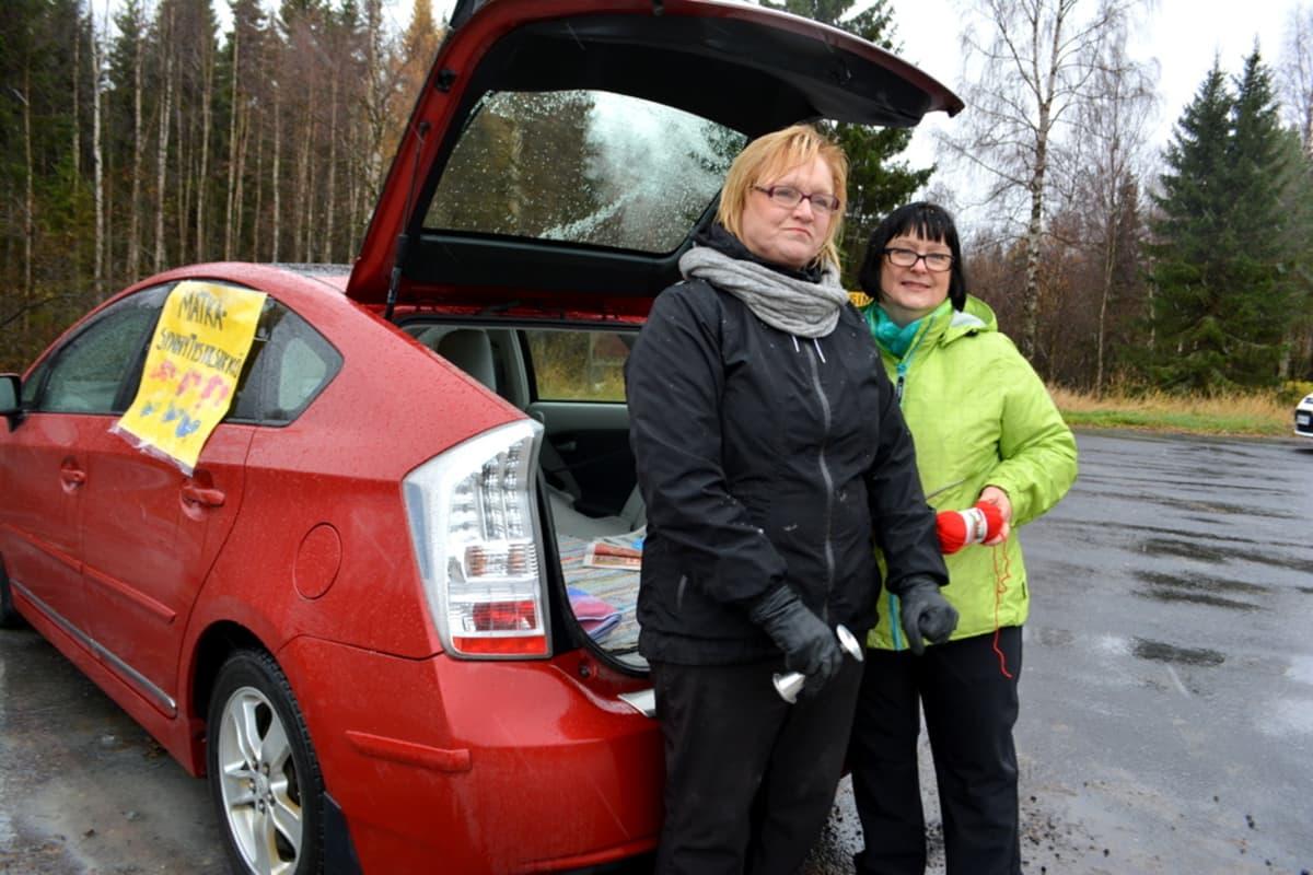 Kaksi naista seisoo auton takana.