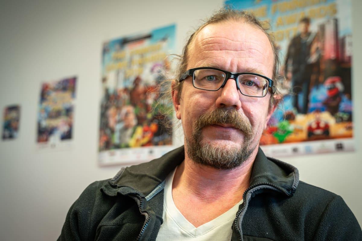 KooPee Hiltunen, direktör för Neogames, tittar in i kameran. I bakgrunden syns planscher på olika spelmässor.