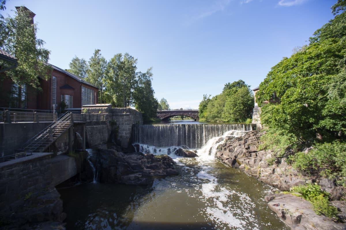 En fors, med en damm och ett vattenfall i mitten. Vattnet är grönbrunt. Det är en solig dag, himlen är blå.