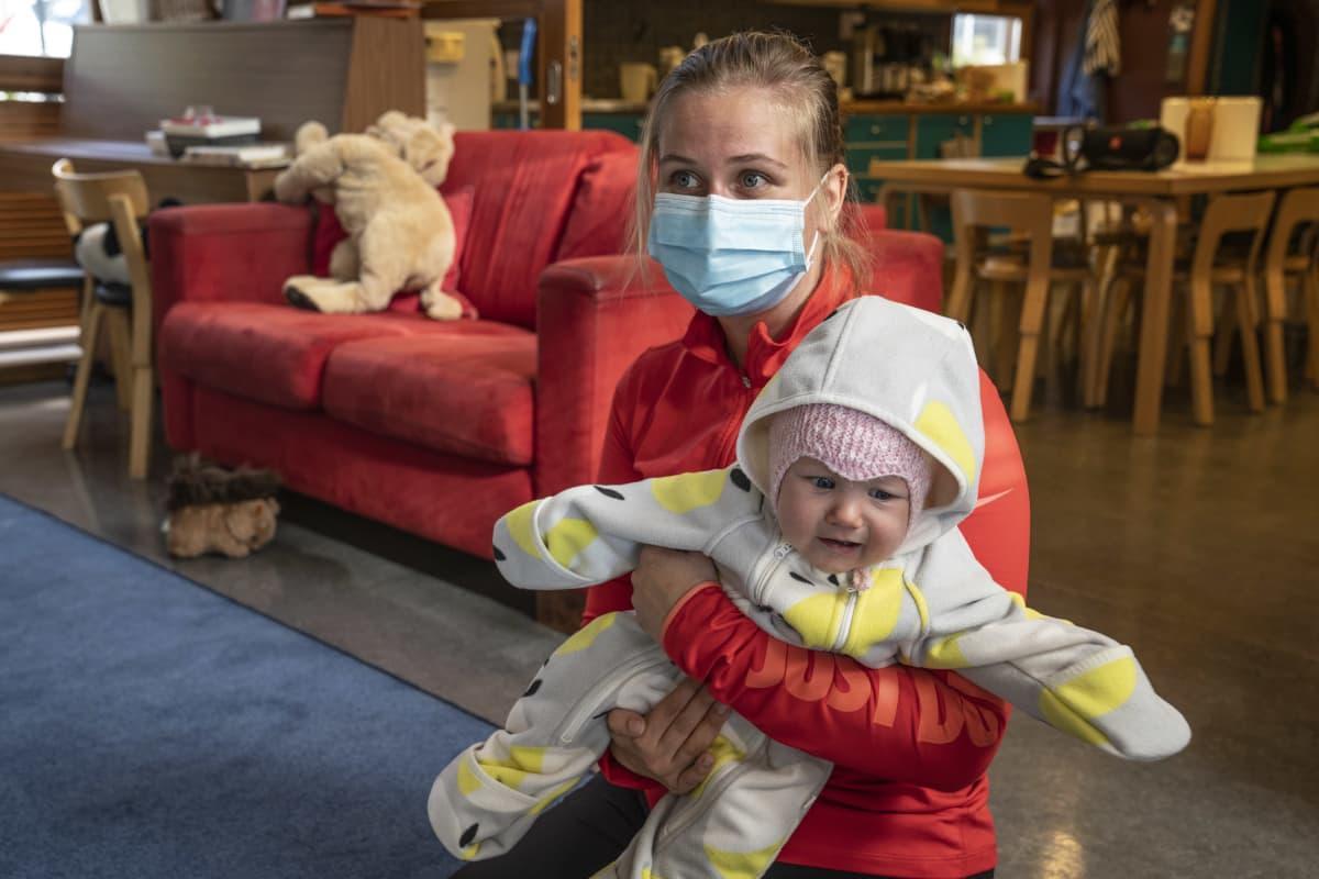 Jenni Föhr-Lundberg pitelee vauvaansa sylissä