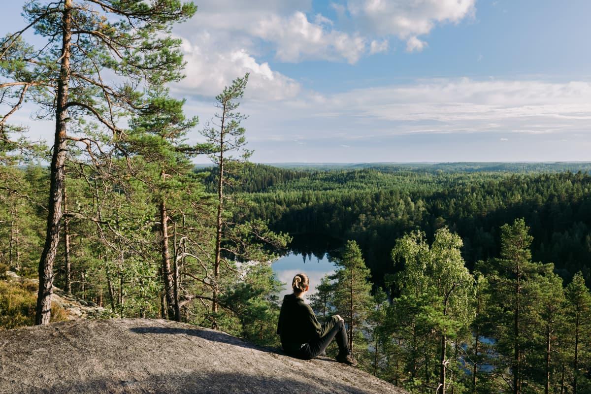 Nainen istuu kallioilla ja katsoo kohti järveä.