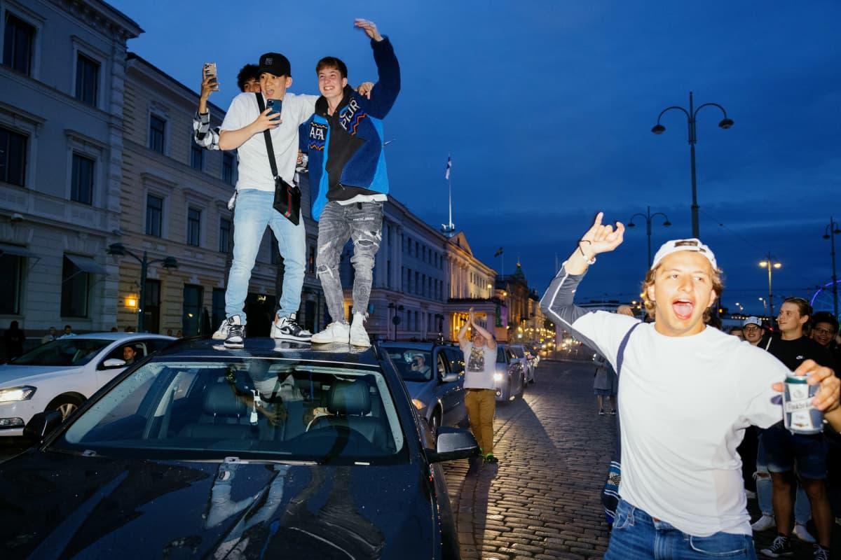 Ihmisiä auton katolla juhlimassa Havis Amandalla.