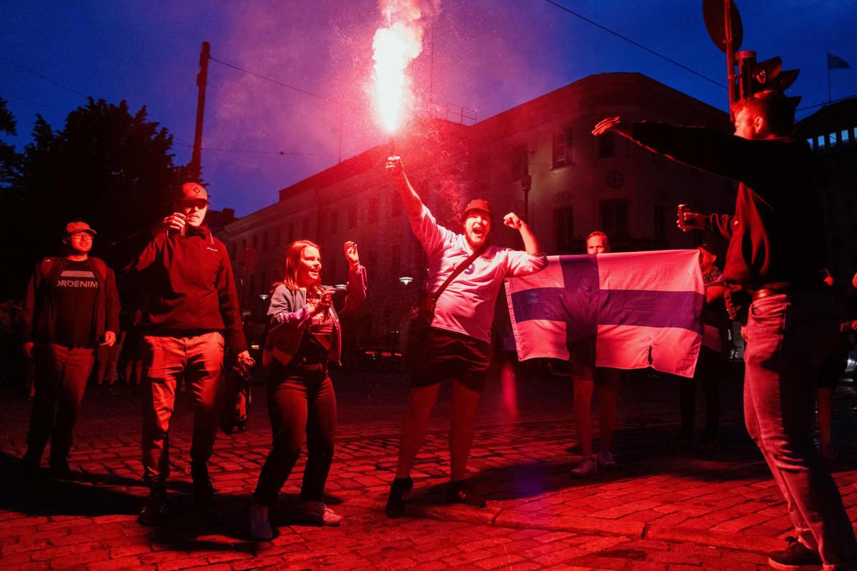 Ihmiset juhlivat soihtu kädessä Huuhkajien voittoa Havis Amandalla.