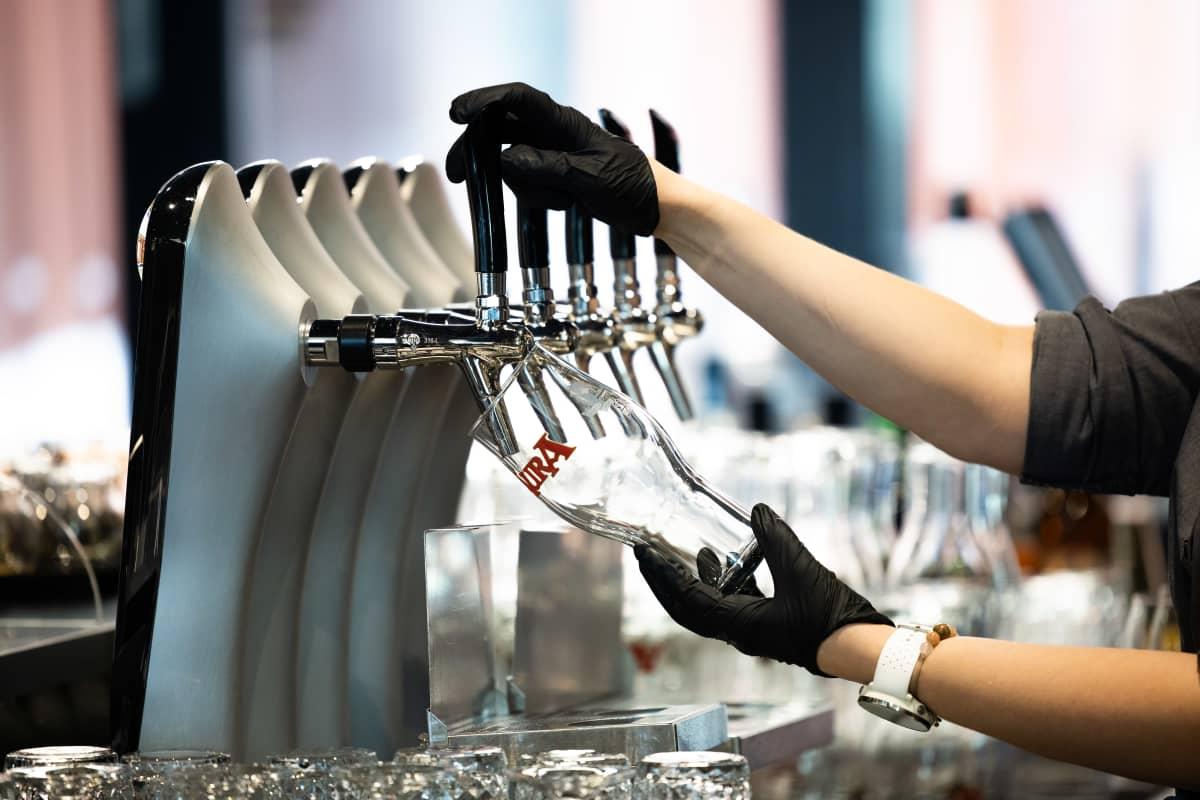 Tarjoilija alkamassa laskemaan olutta tuoppiin.