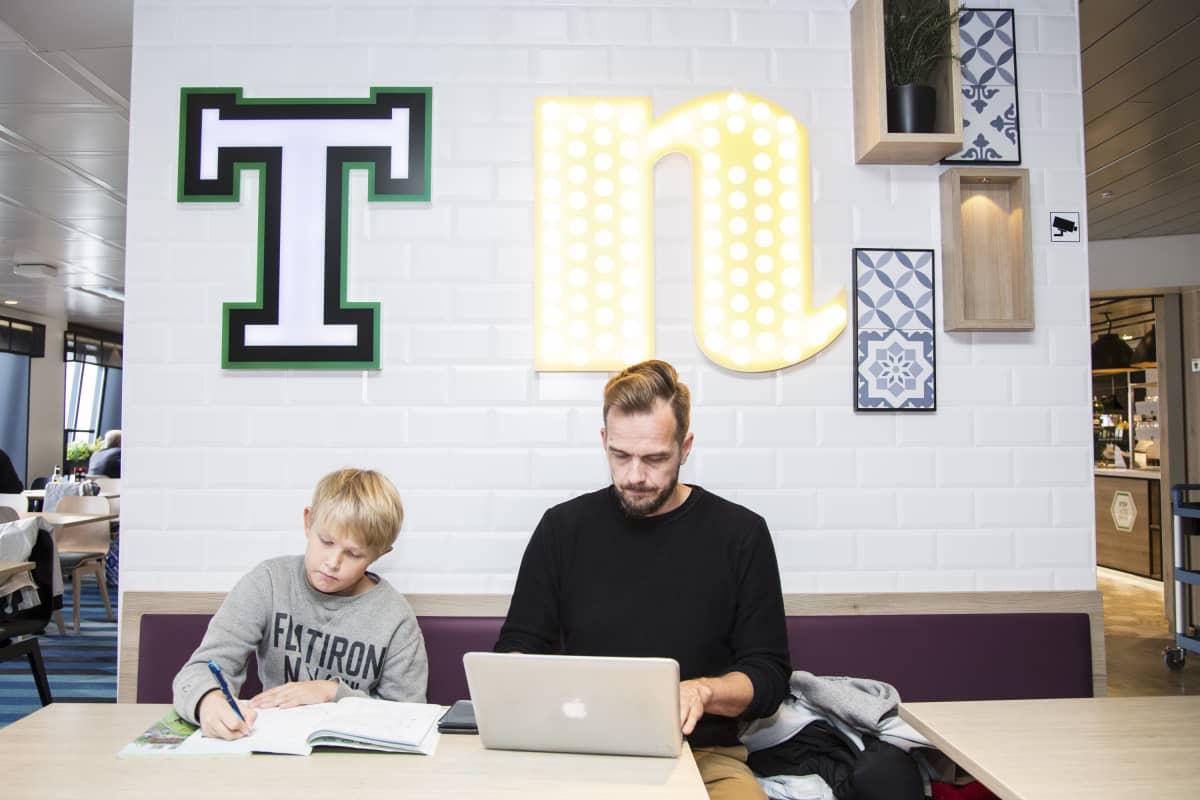 Mies katsoo tietokonetta, poika koulukirjaa.
