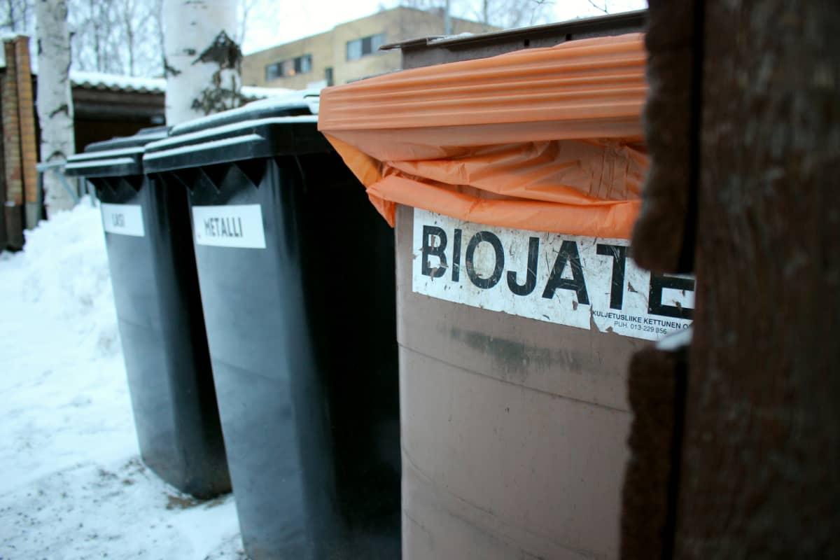 Jäteastiat biojätteelle, metallille ja lasille kerrostalon pihalla.
