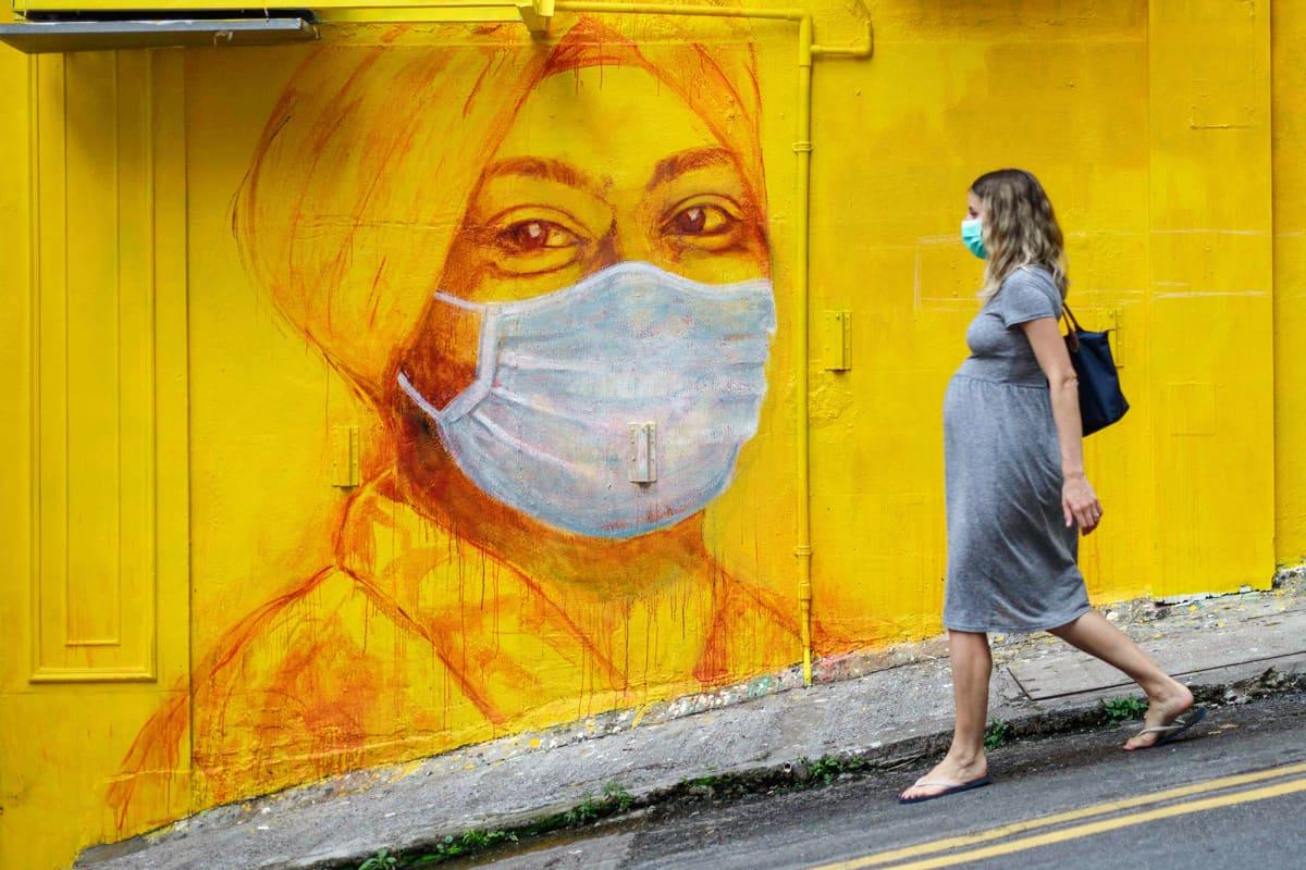 Hengityssuojaimeen pukeutunut raskaana oleva nainen kävelee kadulla Hongkongissa.
