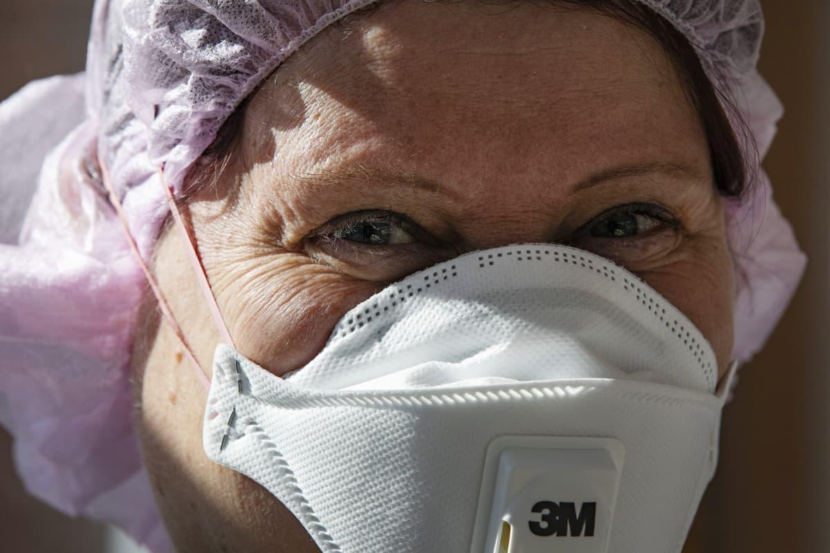 Kuvassa on sairaanhoitaja ja hengityssuoja.