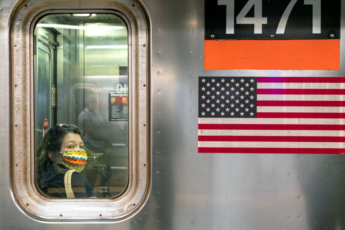 Kasvomaskiin pukeutunut matkustaja New Yorkin metrossa