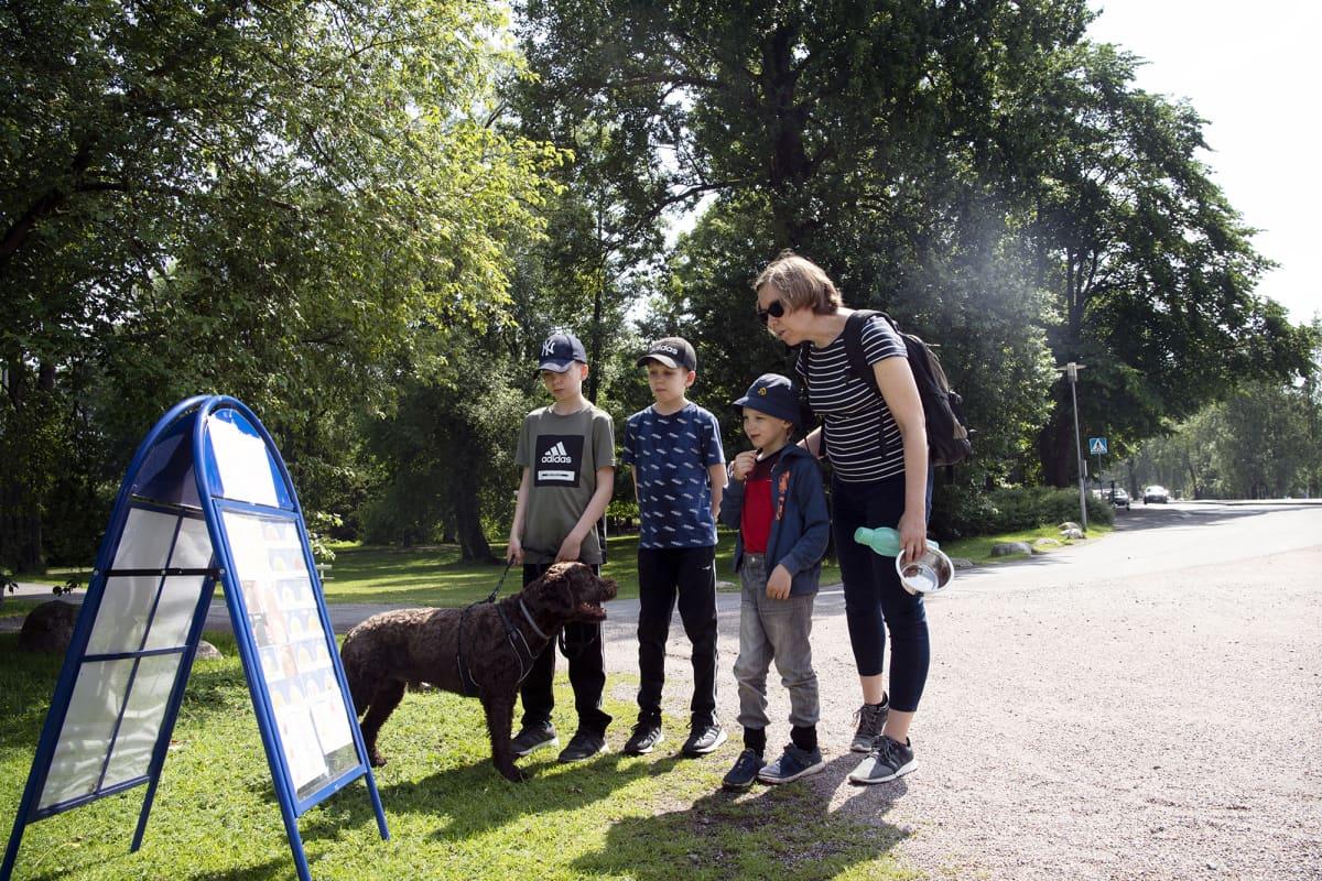 Joel, Emil ja Samuel Koskimäki sekä Heidi Hinkkanen ja portugalinvesikoira Leo Sibeliuspuiston jäätelökioskin edustalla.