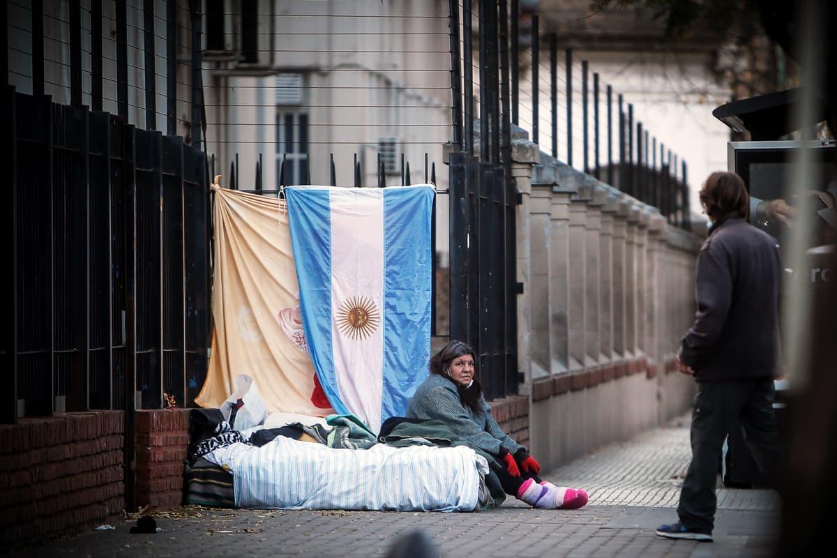 Koditon nainen istuu patjan päällä sairaalan edustalla Buenos Airesissa.