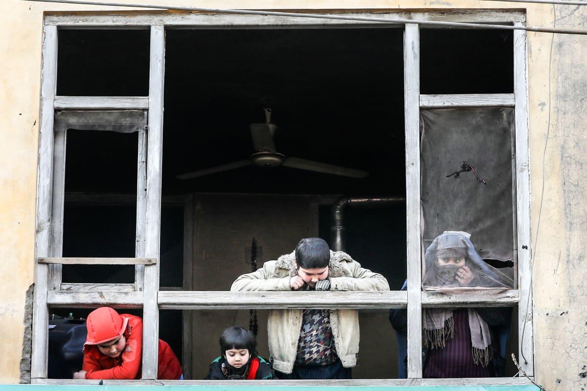 Afgaaniperheen jäseniä katselemassa räjähdyksessä vaurioituneen talon ikkunasta uloa.