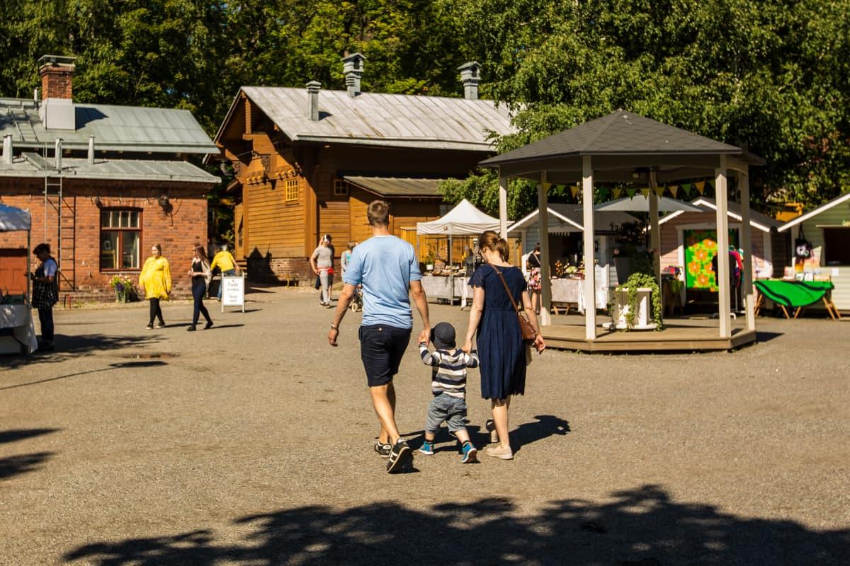 Lapsiperhe Tallipihalla heinäkuussa. Kuvituskuva.