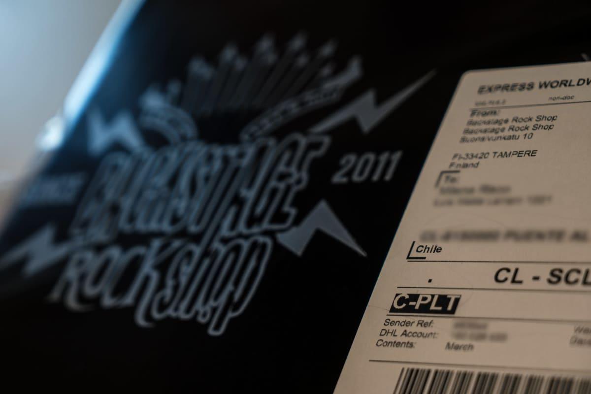 Chileen menevä paketti Backstage Rock Shopin varastossa Tampereella. Sumennettu vastaanottajan nimi ja osoite.