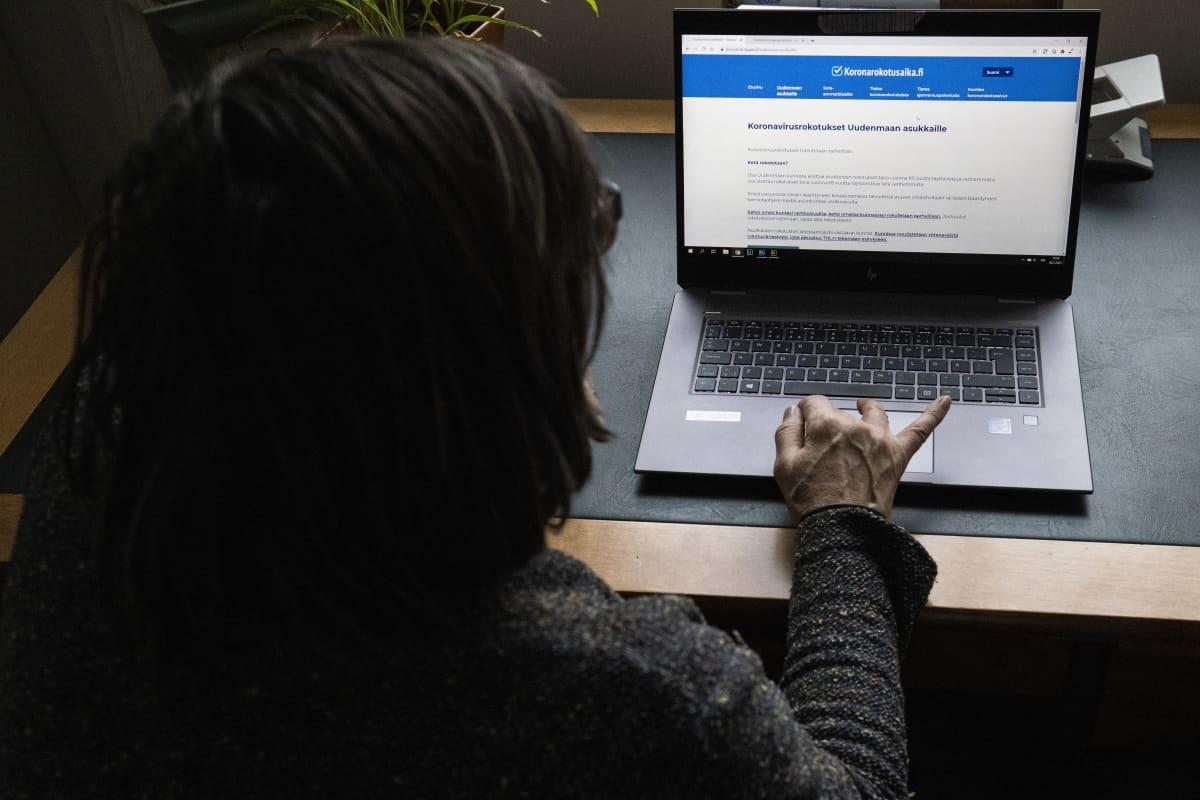 Eläkeikäinen henkilö tutkii Koronarokotusaika.fi sivustoa Espoossa.