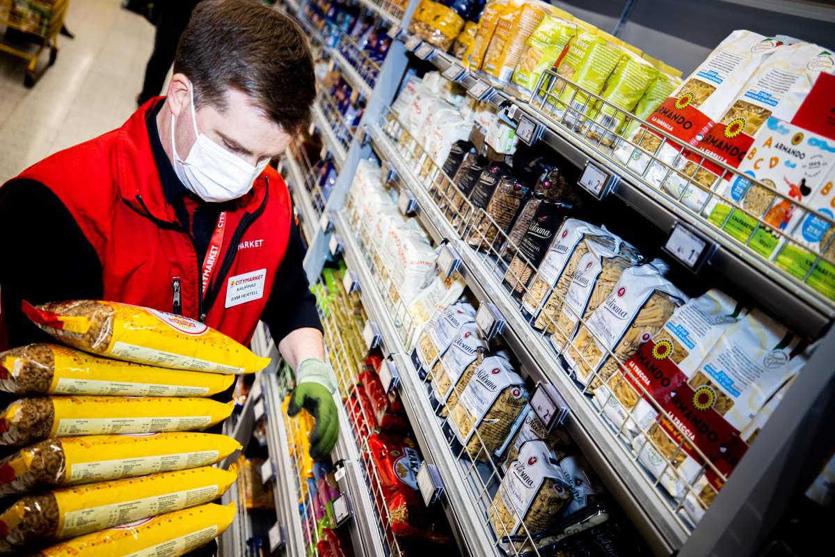 Kauppias Sami Hertell järjestelee pastahyllyjä.