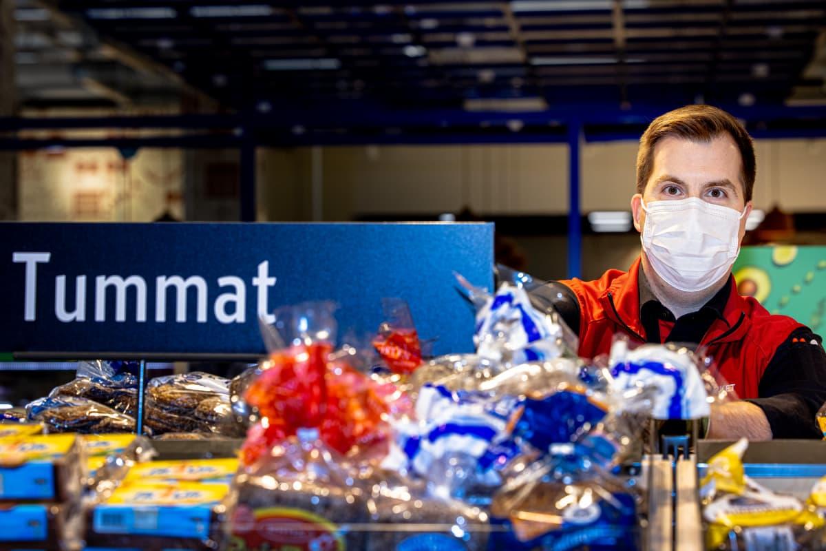 Kauppias Sami Hertell tummien leipien hyllyillä kaupassa.