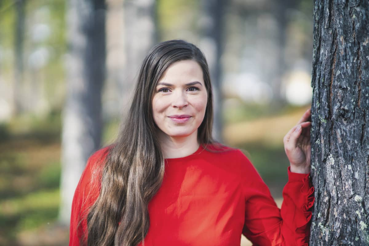 Anni Koivistolla on punainen paita ja hän nojaa puuhun.
