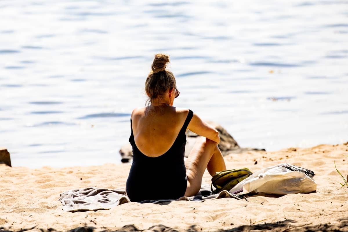 Henkilö istuu uimarannalla uikkareissa.