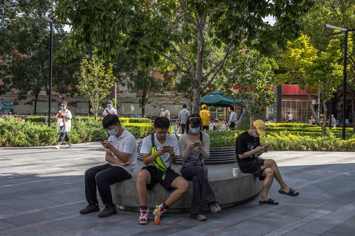 Nuoret puhelimiensa äärellä Kiinan pääkaupungissa Pekingissä Sanlitunin kaupunginosassa. Jatkossa nettipelaamiseen tulee tuntuva leikkaus: vain kolme tuntia viikossa.