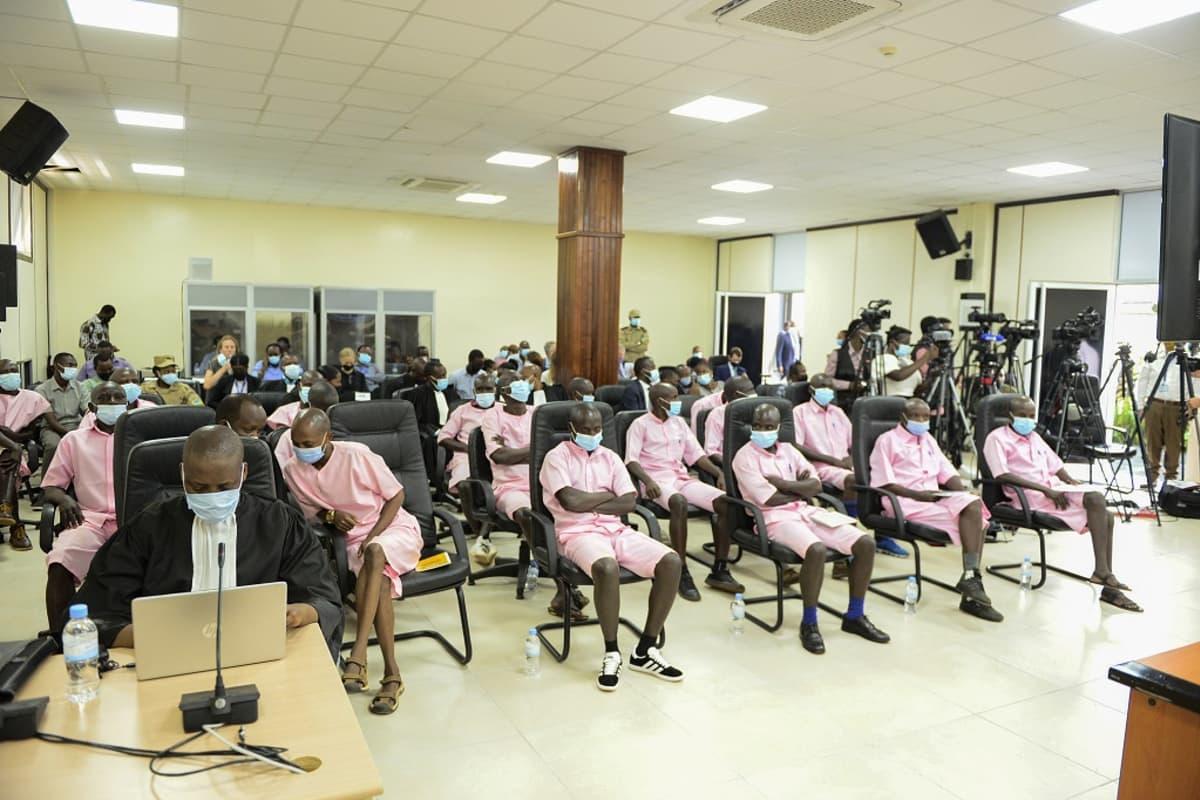 Kuvassa ovat oikeudenkäynnin muut syytetyt puettuina vaaleanpunaisuun vangin asuihin.