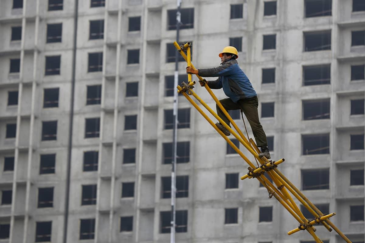 Kiinalainen siirtotyöläinen on kurottautunut kokoamaan metallisia rakennustelineitä Kiinan Pekingissä. Taustalla rakenteilla oleva betoninen kerrostalo.