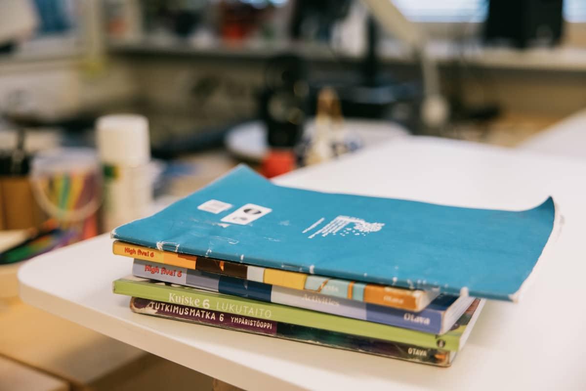 Kirjoja ja vihkoja koulun pöydällä.