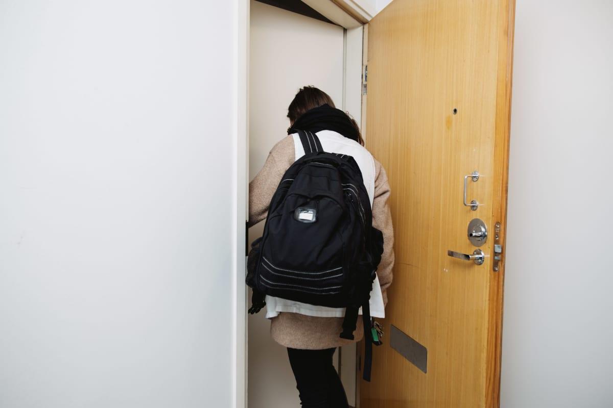 Lähihoitaja astuu asiakkaan asuntoon sisälle.