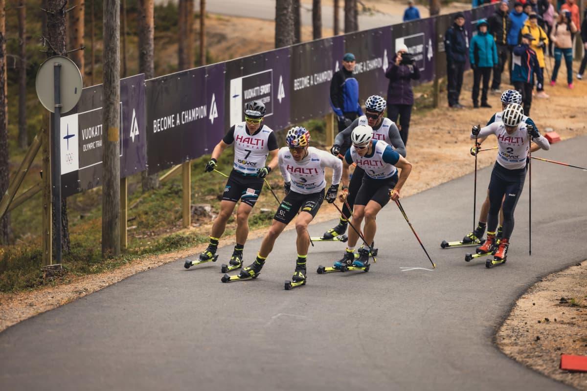 Urheilijat hiihtävät metsässä.