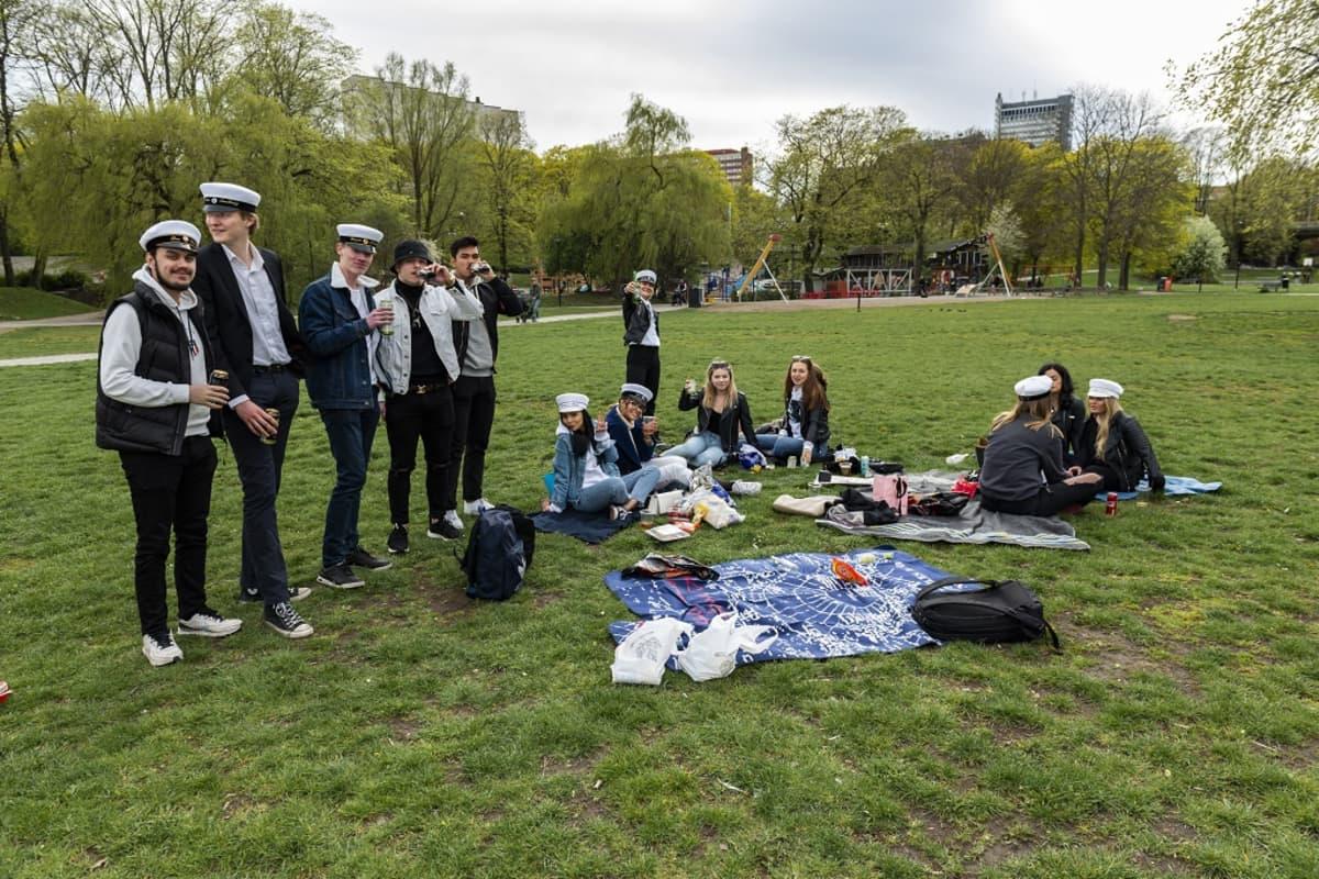Ylioppilaslakkisia nuoria picnicillä puistossa.