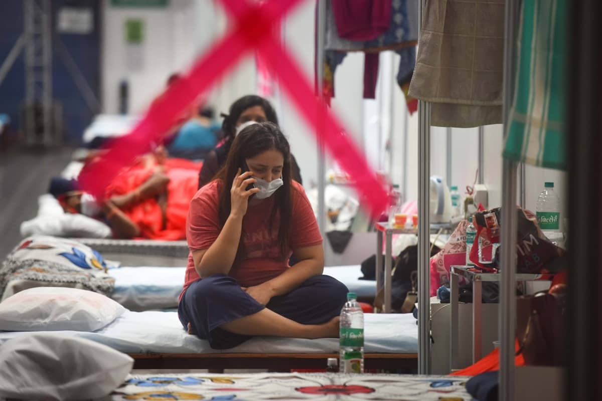 Ikkunan läpi kuvattu näkymä sairaalaan. Maskia pitävä nainen istuu vuoteella ja puhuu puhelimeen.