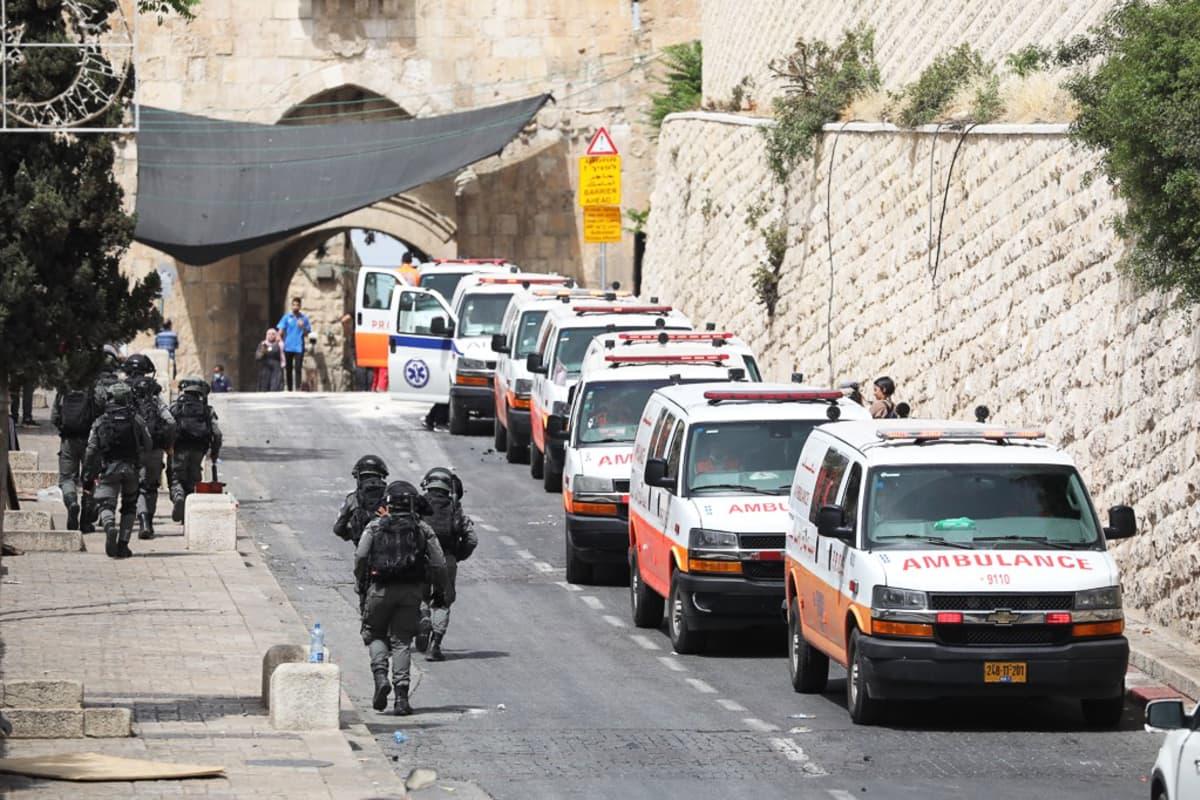 Aseistautuneet israelilaispoliisit kävelivät 10.toukokuuta palestiinalaisambulanssien ohi Temppelivuorella Jerusalemissa.