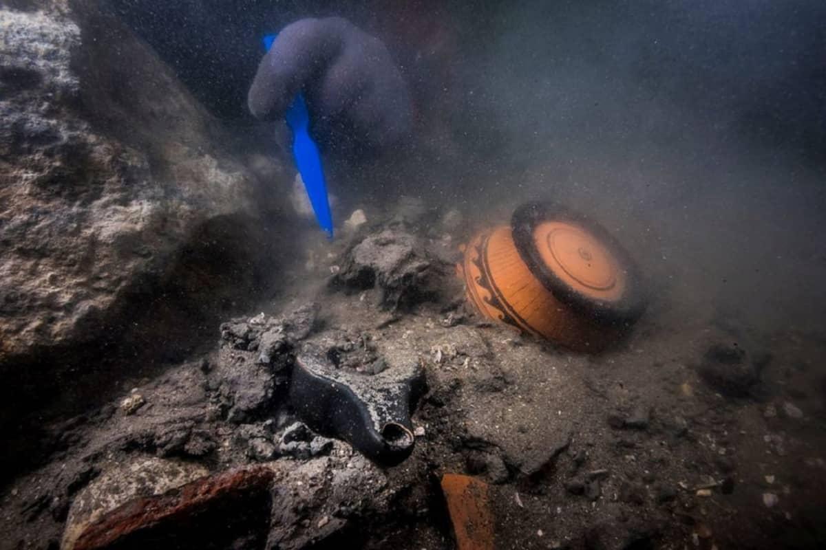 Sukeltaja poistaa hiekkaa merenpohjassa lojuvien astioiden päältä.