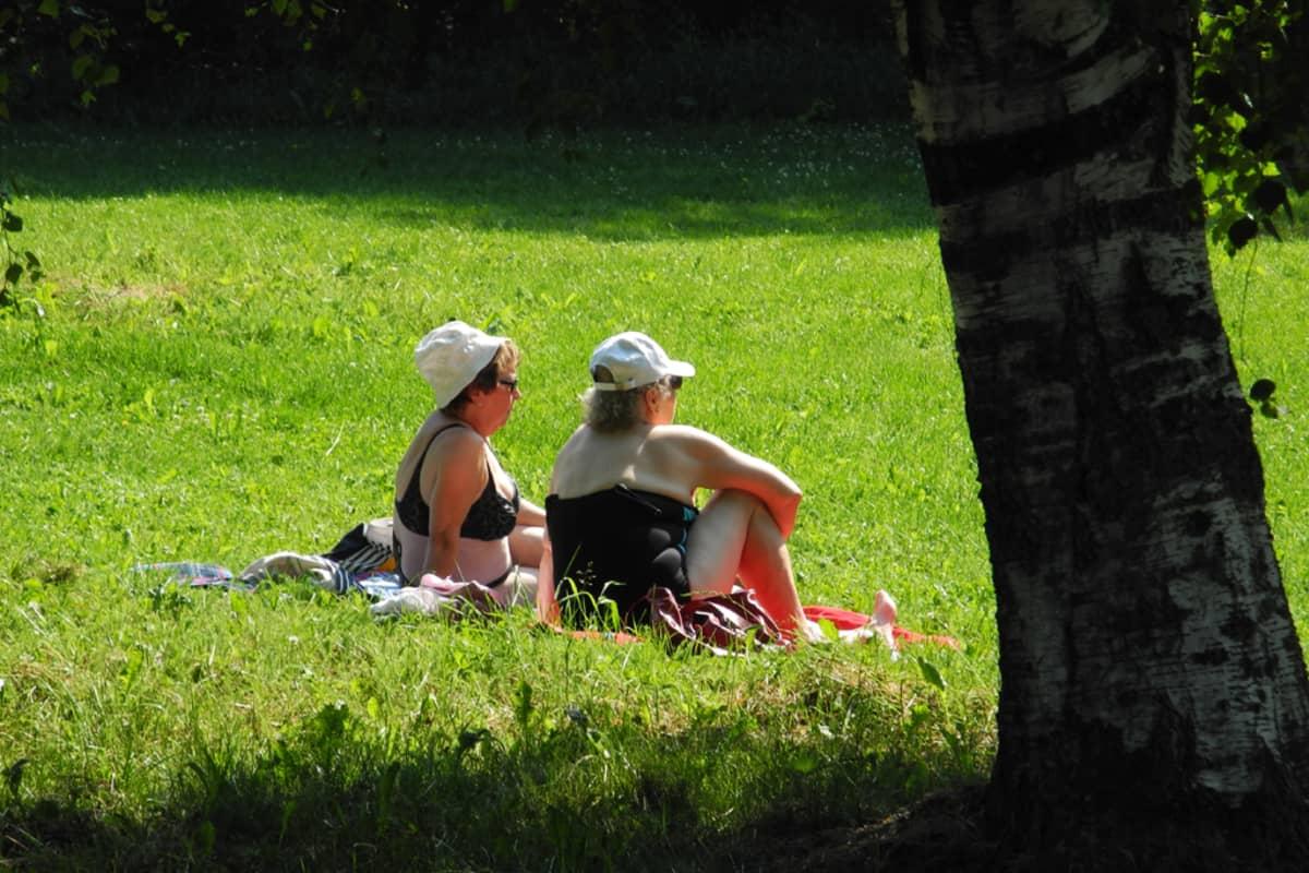 Kaksi naista nurmikolla.