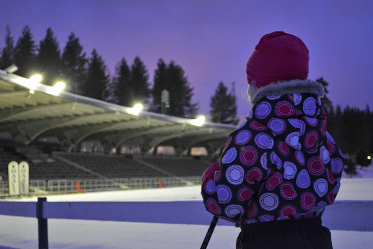 Lapsi seisoo hiihtosauvojen kanssa ja katselee urheilustadionin valoja.